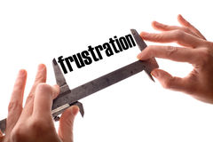 Small frustration. Color horizontal shot of two hands holding a caliper and measuring the word frustration Royalty Free Stock Photo