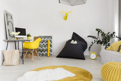Small but functional flat idea. New design light flat with desk, chair, carpet, sack chair, pouf and sofa Royalty Free Stock Photo