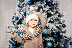 Small funny boy in headdress and body woolen sweater eats chocolate sweets on background of a Christmas tree on the eve of Christm. As home.He ate and smeared Royalty Free Stock Photos