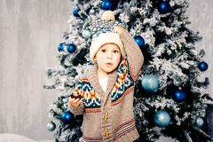 Small funny boy in headdress and body woolen sweater eats chocolate sweets on background of a Christmas tree on the eve of Christm. As home.He ate and smeared Royalty Free Stock Images
