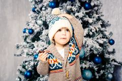 Small funny boy in headdress and body woolen sweater eats chocolate sweets on background of a Christmas tree on the eve of Christm. As home.He ate and smeared Stock Images
