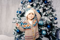 Small funny boy in headdress and body woolen sweater eats chocolate sweets on background of a Christmas tree on the eve of Christm. As home.He ate and smeared Stock Photography