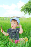 Small, funny girl sitting in the grass Stock Image
