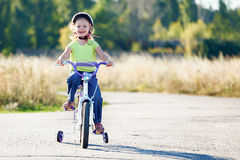 Small funny kid riding bike Stock Photos