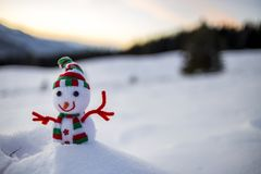 Small funny toy baby snowman in knitted hat and scarf in deep snow outdoor on blurred snow covered mountains landscape background stock images