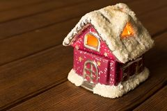 A small funny toy house with glowing Windows. Christmas and New stock photos
