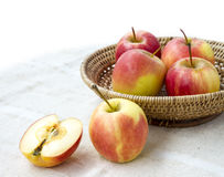 Small gala apple and half in basket on sack background. Royalty Free Stock Photography