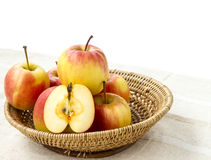 Small gala apple and half in basket on sack over white. Stock Images