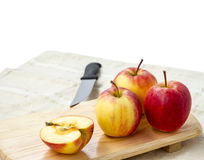Small gala apple on wooden chopping board over white. Royalty Free Stock Image