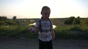 The boy is standing and actively moving the bubble wand in the sun, slow motion stock footage