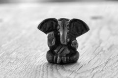 Small Ganesha figure black and white. Beautiful Ganesh statue with open palm monochrome. Asian religion and faith concept. Isolated god sculpture. Religious royalty free stock photos