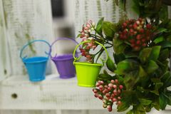 Colorful miniature garden watering can on a background of bushes stock photo