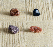 Small garden four stones (minerals). On the sand Royalty Free Stock Photo