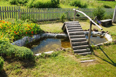 Small garden pond with wooden bridge Royalty Free Stock Images