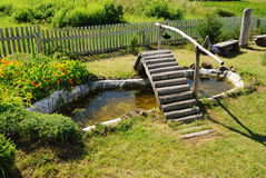 Small garden pond with wooden bridge Royalty Free Stock Photography