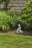 Small Garden Statue. A small garden statue in a garden on a city front yard Stock Photo