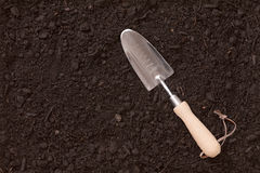 Small garden trowel lying on rich brown earth Stock Photography