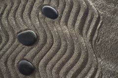 Small Garden zen. Drawings on light gray sand and black stones in a small Zen garden Royalty Free Stock Photo
