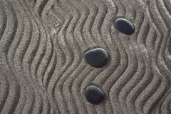 Small Garden zen. Drawings on light gray sand and black stones in a small Zen garden Royalty Free Stock Images