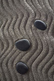 Small Garden zen. Drawings on light gray sand and black stones in a small Zen garden Royalty Free Stock Image