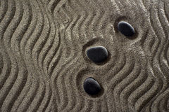 Small Garden zen. Drawings on light gray sand and black stones in a small Zen garden Royalty Free Stock Photos