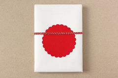 Small gift with blank red gift tag Stock Image