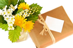 Small gift and bouquet of wild flowers Stock Photos