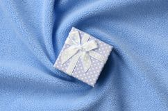 A small gift box in blue with a small bow lies on a blanket of soft and furry light blue fleece fabric with a lot of relief folds. Packing for a gift to your stock images