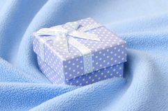 A small gift box in blue with a small bow lies on a blanket of soft and furry light blue fleece fabric with a lot of relief folds. Packing for a gift to your Royalty Free Stock Images
