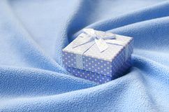 A small gift box in blue with a small bow lies on a blanket of soft and furry light blue fleece fabric with a lot of relief folds. Packing for a gift to your Stock Photos