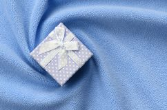 A small gift box in blue with a small bow lies on a blanket of soft and furry light blue fleece fabric with a lot of relief folds. Packing for a gift to your royalty free stock image