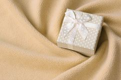A small gift box in orange with a small bow lies on a blanket of soft and furry light orange fleece fabric with a lot of relief. Folds. Packing for a gift to stock images