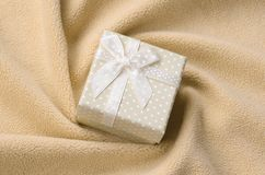 A small gift box in orange with a small bow lies on a blanket of soft and furry light orange fleece fabric with a lot of relief. Folds. Packing for a gift to stock image