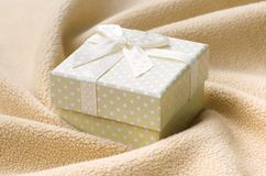 A small gift box in orange with a small bow lies on a blanket of soft and furry light orange fleece fabric with a lot of relief. Folds. Packing for a gift to royalty free stock photography