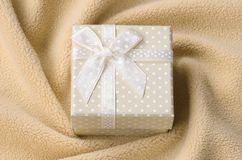 A small gift box in orange with a small bow lies on a blanket of soft and furry light orange fleece fabric with a lot of relief. Folds. Packing for a gift to stock photos