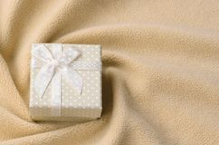 A small gift box in orange with a small bow lies on a blanket of soft and furry light orange fleece fabric with a lot of relief. Folds. Packing for a gift to stock photo