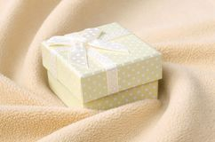 A small gift box in orange with a small bow lies on a blanket of soft and furry light orange fleece fabric with a lot of relief. Folds. Packing for a gift to royalty free stock photo