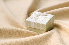 A small gift box in orange with a small bow lies on a blanket of soft and furry light orange fleece fabric with a lot of relief. Folds. Packing for a gift to royalty free stock image