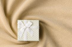 A small gift box in orange with a small bow lies on a blanket of soft and furry light orange fleece fabric with a lot of relief. Folds. Packing for a gift to royalty free stock images