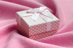 A small gift box in pink with a small bow lies on a blanket of soft and furry light pink fleece fabric with a lot of relief folds. Packing for a gift to your Royalty Free Stock Images
