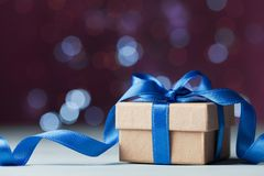 Small gift box or present against magic bokeh background. Holiday greeting card for Christmas or New Year. Royalty Free Stock Photo