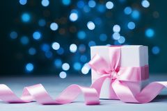 Small gift box or present with pink bow ribbon against magic bokeh background. Greeting card for Christmas, New Year or wedding. Royalty Free Stock Photos