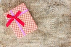 Small gift box on sack cloth Royalty Free Stock Image