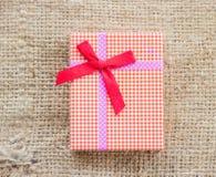Small gift box on sack cloth Royalty Free Stock Photo