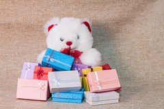 Small gift box set with teddy bear. On sack cloth background Stock Photography