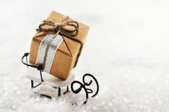 Small gift box on white sledge. Merry Christmas greeting card Royalty Free Stock Images