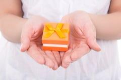 Small gift box in woman hands. Small orange gift box in woman hands royalty free stock images