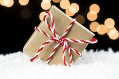 Small gift box wrapped in brown paper and twine wedged in white. Snow. Black background with soft holiday lights. Christmas, holiday sale or event concept royalty free stock images