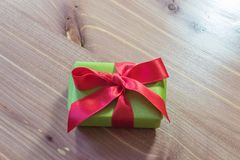 Small gift box wrapped in green paper with a large red satin bow, centered, neutral wood background. Copy space, horizontal aspect Stock Photos