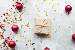 A small gift decorated with Kraft paper and twine on a gray background with gold confetti, red Christmas balls and a garland. The